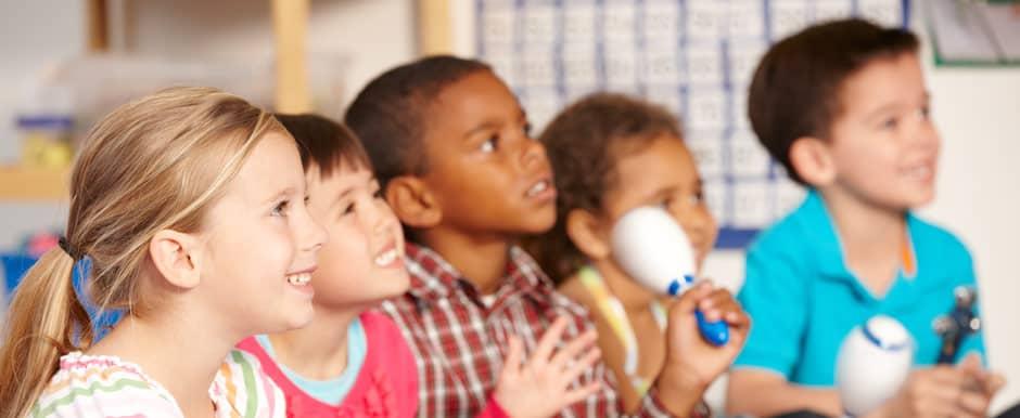 Fünf Kinder hören gespannt zu und lernen Musik